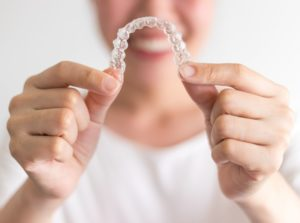 Smiling woman holds up Invisalign in Collierville